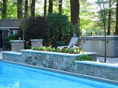Stone columns with matching granite caps mark the entrance to the raised patio. Raised planters with micro drip irrigation allow for seasonal color and small flowering trees.