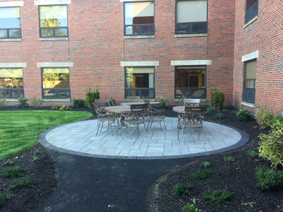 The custom patio, with paver slabs installed in a random pattern with contrasting dark border, is installed in a shady corner near the building.
