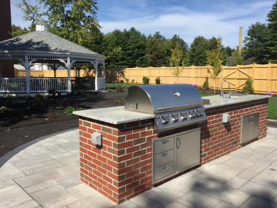The outdoor kitchen is fully equipped with a gas range, prep sink, trash receptacles, and a natural granite slab counter top.