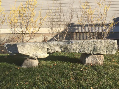 A natural stone bench creates a place to take in the view.