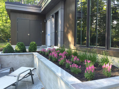 We installed under-drainage piping in this built-in planter, then installed masses of Speedwell and Allium.