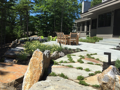 The patio dining area is softened with billowy masses of perennials.