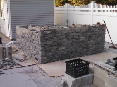 The natural stacked-stone veneer is installed.