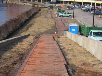 Sidewalk installation in progress. Chain link fence along river to be replaced with wrought iron.